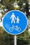 Detformade vägmärket är en gångare- och cykelzon mot en bakgrund av grön lövverk Tecken och cykel för vitt folk arkivbilder