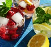 Detox cool drink with ice cubes and fresh raspberries, blueberries and fresh lemon. With mint in assortment. close up.top view Stock Images