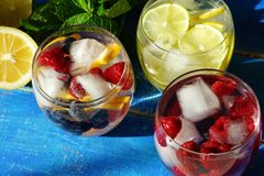 Detox cool drink with ice cubes and fresh raspberries, blueberries and fresh lemon. With mint in assortment. close up.top view Royalty Free Stock Photography