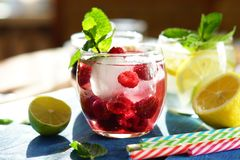 Detox cool drink with ice cubes and fresh raspberries, blueberries and fresh lemon. With mint in assortment. close up Stock Photos