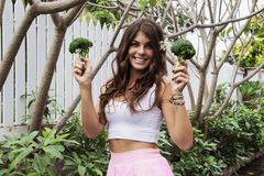 Detox diet: beautiful girl smiling holding broccoli. Outside stock photos