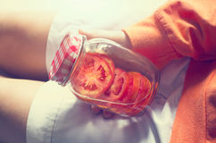 Detox diet fresh red tomato soak in water of the jar in woman hand Royalty Free Stock Photos