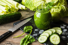 Detox diet. Green smoothie with different vegetables on wooden background stock photo