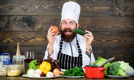 Detox diet. Professional chef in cook uniform. Happy bearded man cooking in kitchen. Dieting with organic food. Fresh. Vegetables. Healthy food and vegetarian royalty free stock photo