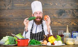 Detox diet. Professional chef in cook uniform. Happy bearded man cooking in kitchen. Dieting with organic food. Fresh. Vegetables. Healthy food and vegetarian stock photography
