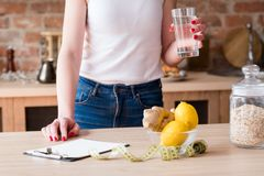 Detox diet slimming weight loss woman lemon ginger. Detox diet for slimming and weightloss. woman holding a glass of water. lemon and ginger laying on the table royalty free stock photography