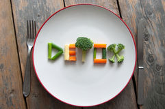 Detox diet. Detox text on a plate made from various vegatables including broccoli, spring onions and carrots Stock Photos