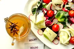 Detox diet with veggie salad and herbal tea. Detox food with vegan salad and herbal tea on a white background . Vegetarian salad with tomato, red iceberg royalty free stock images