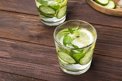 Detox drink with cucumber, lemon and mint in glasses on a wooden. Background. Copy space. Food background royalty free stock images