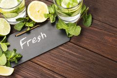 Detox drink with cucumber, lemon and mint on a wooden background. Copy space. Food background Royalty Free Stock Photos