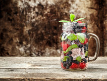 Detox drink with fresh berries in glass jars Royalty Free Stock Photos