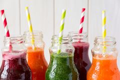 Detox drinks in bottles: fresh smoothies from vegetables: beet, carrot, spinach, cucumber and apple Stock Images