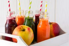 Detox drinks in bottles: fresh smoothies from vegetables: beet, carrot, spinach, cucumber and apple. On white background stock images
