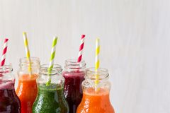Detox drinks in bottles: fresh smoothies from vegetables: beet, carrot, spinach, cucumber and apple. On white background stock image