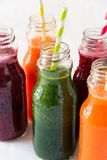 Detox drinks in bottles: fresh smoothies from vegetables: beet, carrot, spinach, cucumber and apple. On white background royalty free stock photography