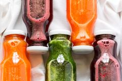 Detox drinks in bottles: fresh smoothies from vegetables: beet, carrot, spinach, cucumber and apple Royalty Free Stock Photos