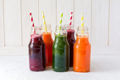 Detox drinks in bottles: fresh smoothies from vegetables: beetroot, carrot, spinach, cucumber and apple. On white background royalty free stock images