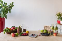 Detox drinks and organic food. Detox drinks and various organic fruits, vegetables and berries on wooden table royalty free stock photography
