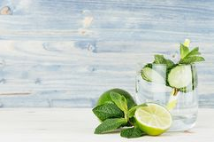 Detox fitness mineral water with cucumber, lime, mint and straw on soft shabby wood background. Royalty Free Stock Photography