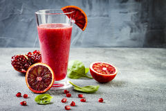 Detox fresh juice or smoothie in glass with blood oranges, greens, pomegranate. Homemade refreshing fruit beverage. Copy space. Detox fresh juice or smoothie in royalty free stock photo