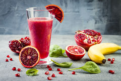Detox fresh juice or smoothie in glass with blood oranges, greens, pomegranate. Homemade refreshing fruit beverage. Copy space. Detox fresh juice or smoothie in stock photos