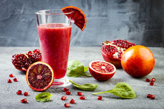Detox fresh juice or smoothie in glass with blood oranges, greens, pomegranate. Homemade refreshing fruit beverage. Copy space. Royalty Free Stock Images