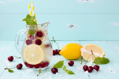 Detox fruit infused flavored water with cherry, lemon and mint. Refreshing summer homemade cocktail. Clean eating royalty free stock photography