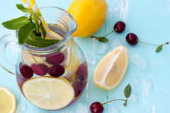 Detox fruit infused flavored water with cherry, lemon and mint. Refreshing summer homemade cocktail. Top view stock photos