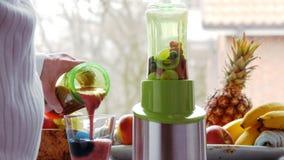 Detox: hälla den nytt blandade smoothien in i exponeringsglas arkivfilmer