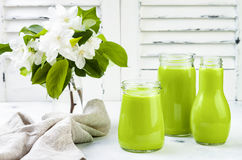 Detox, healthy green smoothie in jars and bottle. White wooden rustic background with apple blossom. Stock Photography