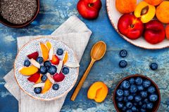 Detox and healthy superfoods breakfast bowl concept. Vegan coconut milk chia seeds pudding over rustic table with various fruits royalty free stock photos