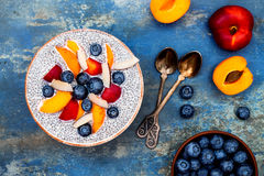 Detox and healthy superfoods breakfast bowl concept. Vegan coconut milk chia seeds pudding over rustic table with various fruits royalty free stock images