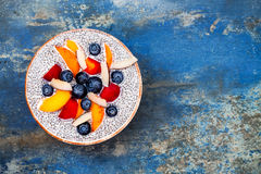 Detox and healthy superfoods breakfast bowl concept. Vegan coconut milk chia seeds pudding over rustic table with various fruits Stock Image