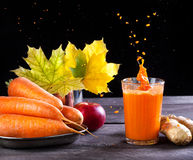 Detox juice. Fresh carrot, apple, ginger juice with splashes on wooden background in autumn season Stock Images