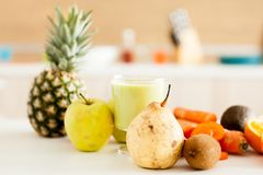 Detox juice next to fruits and vegetables. At the kitchen royalty free stock photo