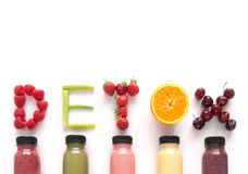 Detox juice smoothies. Detox word made with fruits from assorted fruit smoothies over a white background stock image