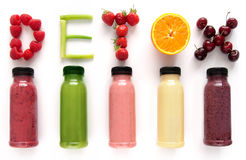 Detox juice smoothies. Detox word made with fruits from assorted fruit smoothies over a white background royalty free stock images