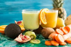 Detox juices next to fruits and vegetables Stock Photo
