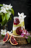 Detox layered matcha green tea chia seed pudding with blood oranges. Vegan dessert with coconut whipped cream. Stock Photo