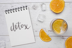 Detox lettering. White wooden background with oranges and drink. Royalty Free Stock Image