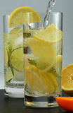 Detox mineral water with lime and lemon. On a light background Royalty Free Stock Images