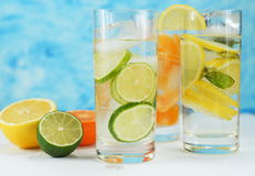 Detox mineral water with lime, tangerine and lemon. On a light background Royalty Free Stock Photos