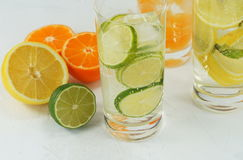 Detox mineral water with lime, tangerine and lemon. On a light background Royalty Free Stock Photo