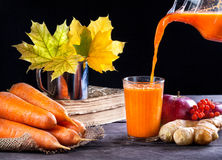 Detox mixed juice. Fresh carrot, apple, ginger juice on wooden background in autumn season Stock Photography