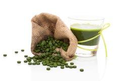 Detox. Pilules vertes avec du jus vert. photographie stock libre de droits