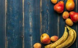 Detox: rozrzucanie świezi dojrzali banany, bonkrety i morele na drewnianym błękita stole, kosmos kopii obraz royalty free