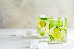 Detox sassy water with cucumber and lemon in glass, light background. Healthy eating concept