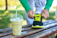 Detox smoothie drink and running footwear close up. Man athlete tying sport shoes. Detox smoothie drink and running footwear close up stock photo