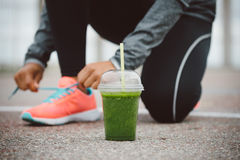 Detox smoothie for healthy fitness nutrition and workout concept. Detox smoothie drink and running footwear close up. City outdoor workout and fitness healthy stock images