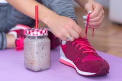 Detox smoothie in retro jar and young woman lacing sport footwear. Healthy fruits detox smoothie in retro jar and young woman lacing sport footwear on purple royalty free stock images